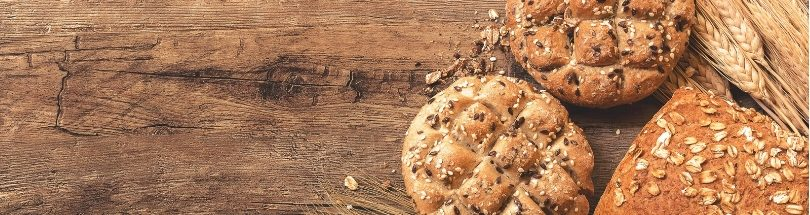Bread and wheat on a wooden surface.