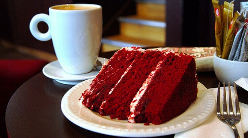 Slice of red velvet cake on white dish ware next to a white coffee mug.